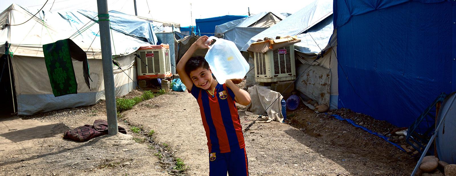 a boy with jerrycan at Cholera Yemen