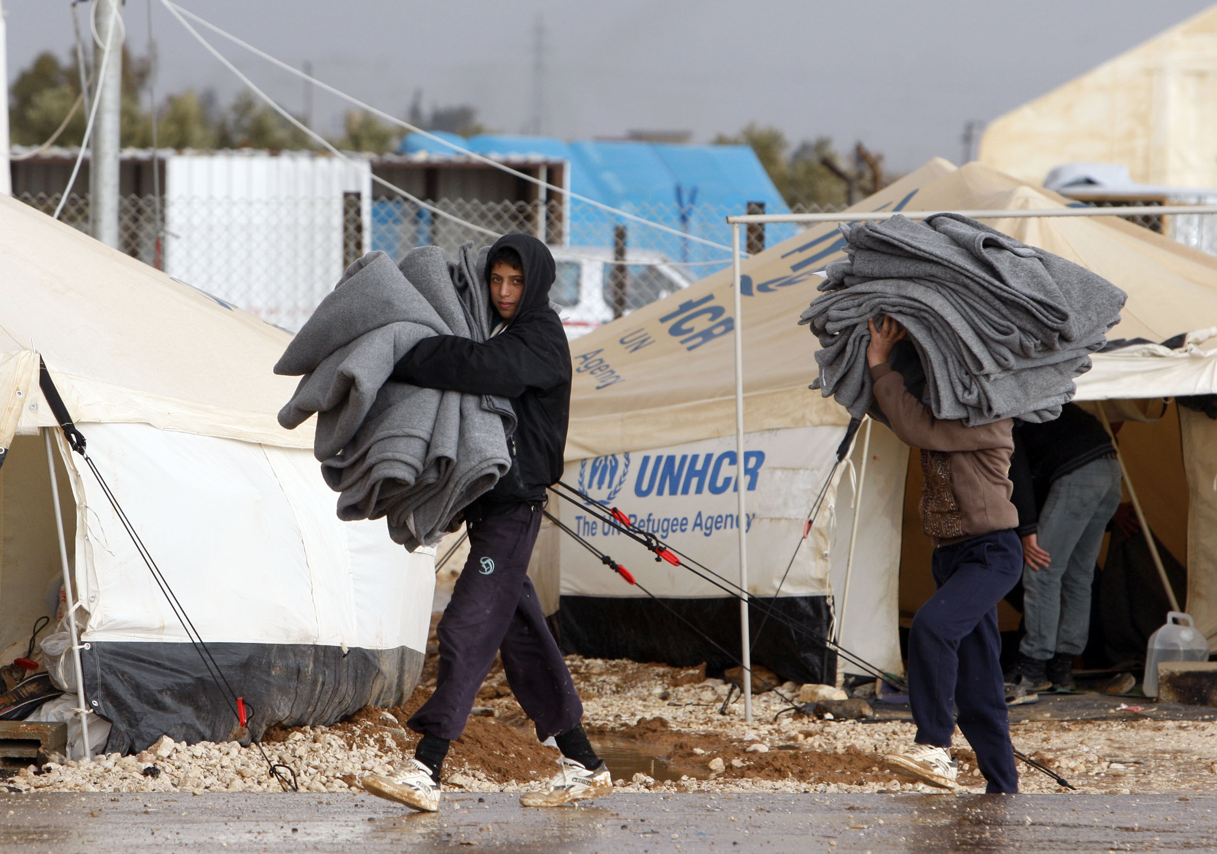 epa03528991 Syrian refugees carry blankets at Zattari Syrian refugee camp, near city of Mafraq, Jordan, 09 January 2013. According to media reports, riots erupted on 08 January 2013 in the Zaatari Syrian refugee camp which was pounded by heavy rains for a second day, damaging 500 tents and submerging much of the site under one meter of mud. EPA/JAMAL NASRALLAH | Blankets