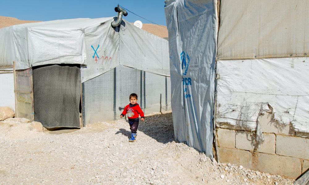 Arsal camp Lebanon 2018 refugee running in front of NRS Relief tents