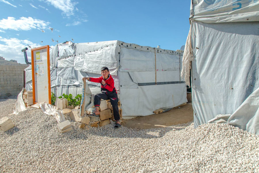 Arsal camp Lebanon 2018 refugee sitting in front of NRS Relief tents