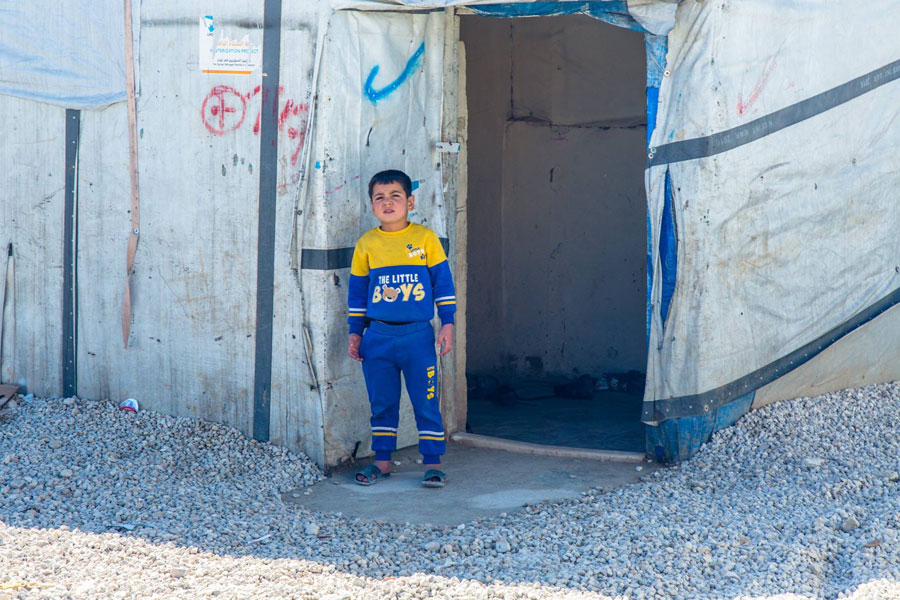 child standing in front of NRS Relief Arsal camp Lebanon 2018