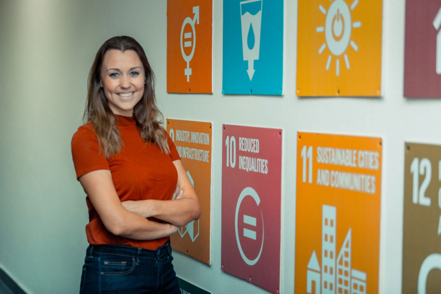 NRS International employee in front of SDGs wall view