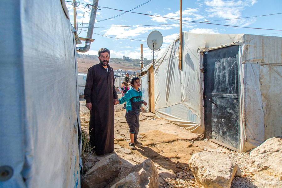 NRS Relief Arsal camp Lebanon 2018 refugee standing in front of refugee tent