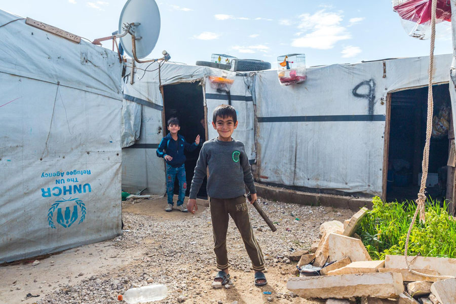 refugee standing in front of NRS Relief Arsal camp Lebanon 2018