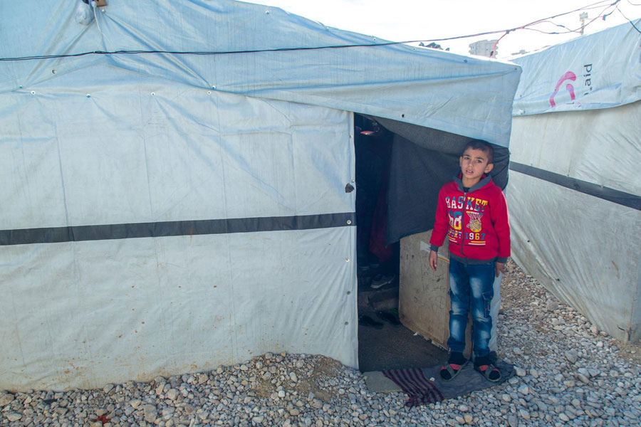 refugee standing in front of tent door at NRS Relief Arsal camp Lebanon 2018