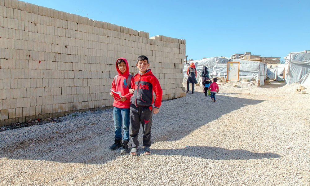 refugees standing in front of wall at NRS Relief Arsal camp Lebanon 2018