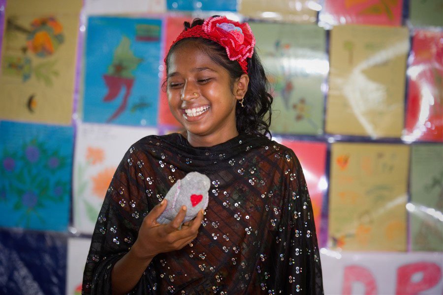 Rohingya refugee girl smiling with Peacedoves in he hands in Bangladesh 2018