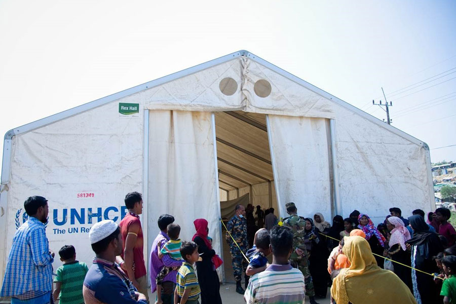 refugees standing front gate of MSU tent by NRS Relief at Kutupalong Bangladesh