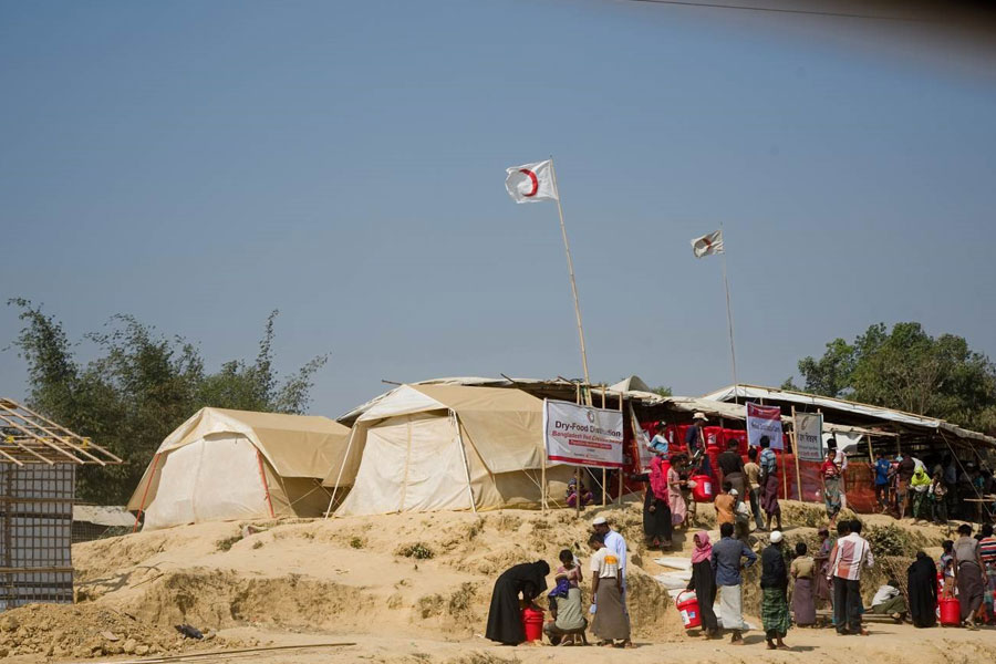 refugees standing MSU UNHCR standard tent by NRS Relief in Kutupalong Bangladesh
