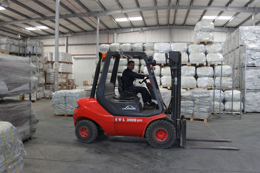 car lifter in front of packages at NRS Relief logistics in Dubai warehouse 2016