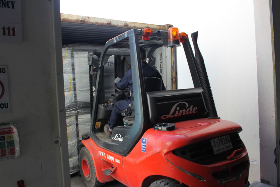 car lifter pulling packages into container at NRS Relief logistics in Dubai warehouse 2016