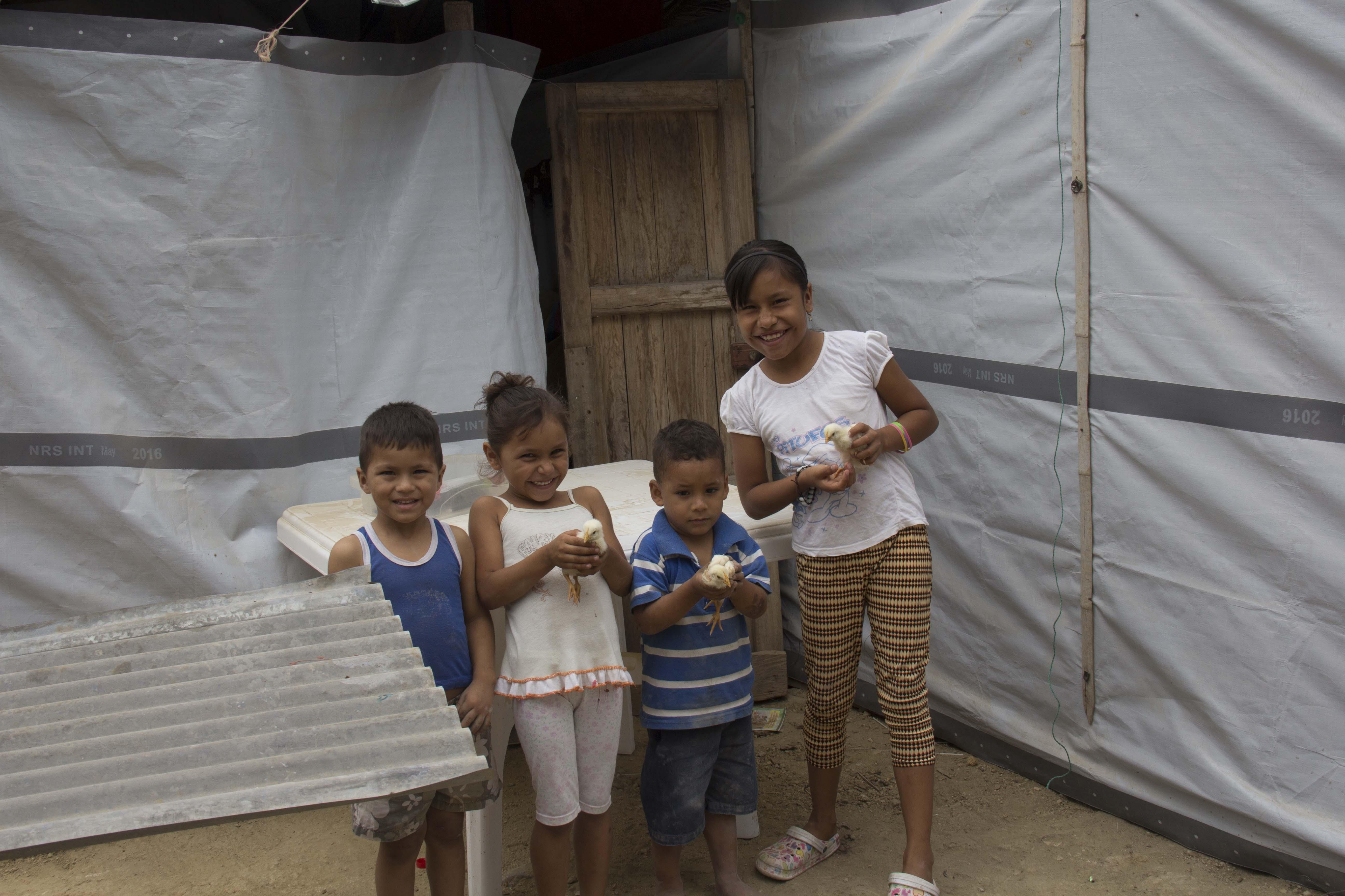 refugee kids smiling in front of tarpaulins at Ecuador in 2016