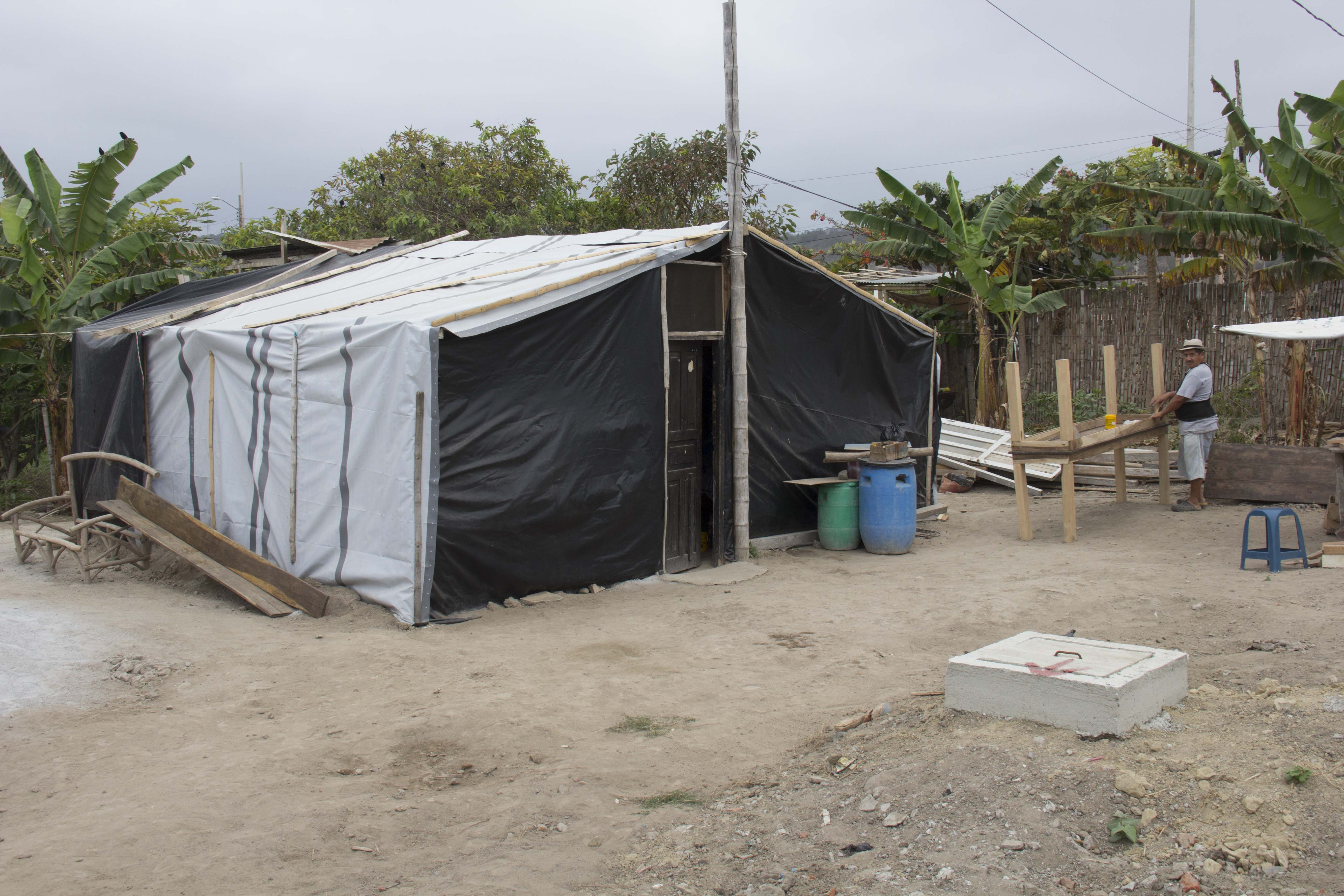 refugee standing in front of their shelter in Ecuador in 2016