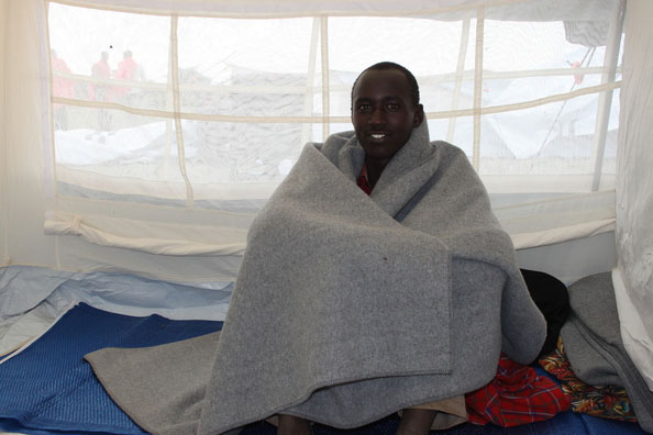 refugee boy sitting in tent of NRS Relief in Kenya 2015